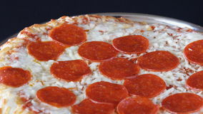 Italian Cuisine: Pepperoni Pizza Slowly Turning in Display stock footage