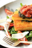 Italian cuisine polenta served with bolognese sauce and lettuce royalty free stock photography