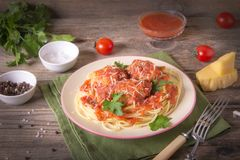 Italian cuisine spaghetti with meatballs noodles pasta meal in a plate on a rustic wooden background.  royalty free stock image