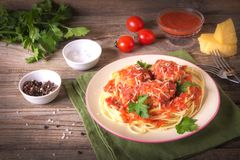 Italian cuisine spaghetti with meatballs noodles pasta meal in a plate on a rustic wooden background.  royalty free stock photo