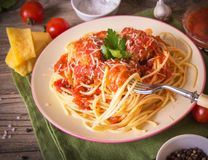 Italian cuisine spaghetti with meatballs noodles pasta meal in a plate on a rustic wooden background.  royalty free stock photography