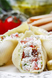 Italian cuisine: stuffed pasta shells and stack of breadsticks Royalty Free Stock Photos