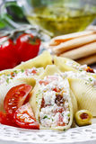 Italian cuisine: stuffed pasta shells and stack of breadsticks Stock Photos