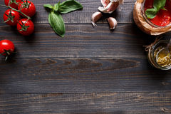 Italian Cuisine. Tomato, basil, garlic and tomato sauce on the dark wooden table top view, with copy space.  Stock Images