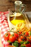 Italian cuisine. Vegetables, oil, spices and pasta on the table Royalty Free Stock Images