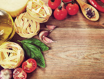 Italian cuisine. Vegetables, oil, spices and pasta on the table. Royalty Free Stock Images