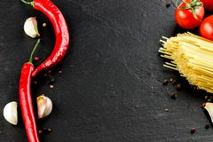Italian cuisine. Vegetables,  spices and pasta on dark backgroun Stock Image