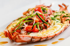 Italian cuisine. Whole lobster baked and sliced in half Served with tomato salad and sauce on white plate. On marble serface stock photo