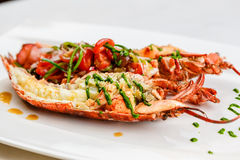 Italian cuisine. Whole lobster baked and sliced in half Served with tomato salad and sauce on white plate. On marble serface royalty free stock photos