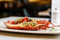 Italian cuisine. Whole lobster baked and sliced in half Served with tomato salad and sauce on white plate. On marble serface royalty free stock images