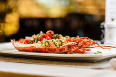 Italian cuisine. Whole lobster baked and sliced in half Served with tomato salad and sauce on white plate. On marble serface royalty free stock photo