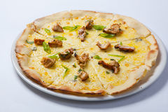 Italian delicious pizza with chicken, cheese and ham. Royalty Free Stock Photo