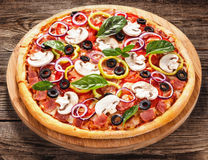 Italian delicious pizza with mushrooms and ham on the old boards Stock Image