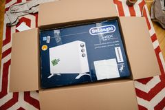 Italian DeLonghi air convection heater bought from Amazon Wareh. PARIS, FRANCE - FEB 7, 2018: Unboxing large cardboard box containing italian DeLonghi air royalty free stock photos