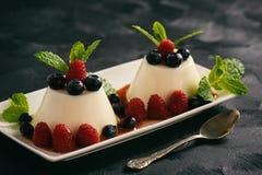 Italian dessert - panna cotta with berries and caramel sauce. Stock Image