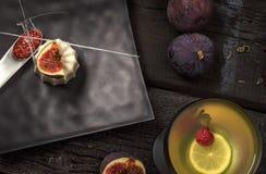 Italian dessert panna cotta. Italian dessert - Vanilla panna cotta with figs and raspberry sauce. Black plate and background and golden cocktail stock photography