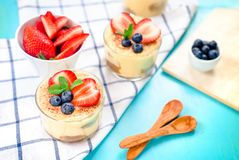 homemade, exquisite dessert tiramisu in glasses decorated with strawberry, blueberry, mint on blue wooden table stock images