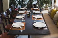 Italian dinner table for eight with cutleries, plates, glasses, napkins and naperies on the table stock photography