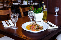 Italian dish of small fish with slices of tomato. Traditional Italian dish of fried small fish with slices of tomatoes and bread on a dark wooden table stock photography