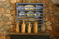 Italian dishes and bottles. Plates on wooden shelves and wicker bottles on table in front of stone wall Stock Image