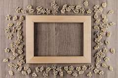 Italian dry sea pasta on beige brown wooden board with empty copy space as decorative frame background. Stock Photo