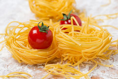 Italian egg pasta nest, cherry tomatoes on a board Royalty Free Stock Photo