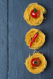 Italian egg pasta nest with cherry tomatoes and chili, concept Stock Image