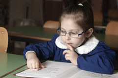 Italian elementary school girl first-grader reading on school Stock Images