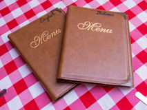 Italian and English menus. Menus in Italian and English language on the table of an Italian restaurant with typical red and white checkered tablecloth Stock Photo