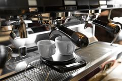Italian espresso machine on a counter in a restaurant dispensing freshly brewed coffee into two small cups