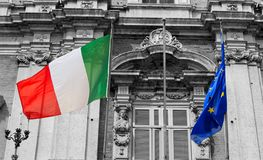 Italian and european flags on a balcony of the italian army academy waving in the wind. Modena, ducal palace royalty free stock image