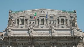 Italian and European flags fluttering in the wind on Milan Central Station.  stock video