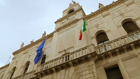 Italian and European flags on the historic building of Town Hall of Padua. Palazzo Moroni, Comune di Padova, shooting from the bottom of. Palazzo Moroni - seat stock video footage