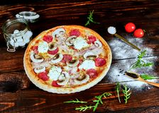 Italian fast food. Delicious hot pizza sliced and served on wooden platter with ingredients, close up view. Menu photo royalty free stock photo
