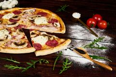 Italian fast food. Delicious hot pizza sliced and served on wooden platter with ingredients, close up view. Menu photo stock images
