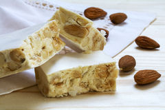 Italian festive torrone or white nougat with almonds, close up Stock Photos
