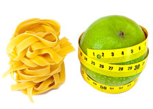 Italian fettuccine nest pasta and apple with measuring tape Royalty Free Stock Photo