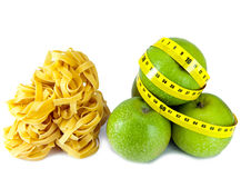 Italian fettuccine nest pasta and apple with a measuring tape.Still-life on a white background Stock Photos