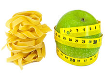 Italian fettuccine nest pasta and apple with a measuring tape on a white background Stock Photo