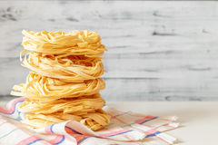 Italian Fettuccine nest pasta on light background Royalty Free Stock Images