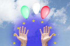 Italian financial Euro crisis concept: three balloons with Italian flag colors rising up to the sky, two hands and the European U stock photo