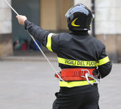Italian firefighter with protective helmet and a rope and the wo Royalty Free Stock Photography