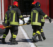 italian firefighters in action carry a stretcher with injured af Stock Photos