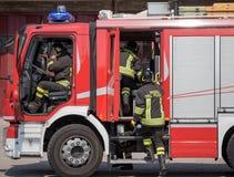 Italian firefighters climb on firetrucks Stock Photo