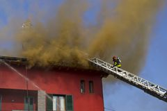 Firemans on a roof fire Stock Images