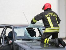 Italian firemen break the windshield of the car to release the i Royalty Free Stock Photos