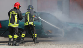 Italian firemen extinguished the car fire after the car accident. Two Italian firemen extinguished the car fire after the car accident with the words in the suit stock images