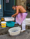 Italian fisherman. Cleaning freshly caught fish on the street in Corniglia, Cinque Terre, Italy Stock Image