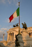 Italian flag with Altare del Patria on the background. Victor Emmanuele II memorial in Rome lit by the soft evening sun Stock Photo