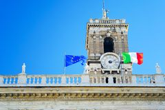 Italian flag, blue sky, clock. Good quality bright photo of italian and european union flags. You may see tall flag poles at the top of some historic building Royalty Free Stock Images